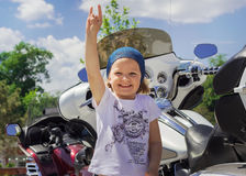 Funny little girl near motorcycles. Royalty Free Stock Photos