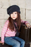 Funny little girl with old suitcases Stock Photos