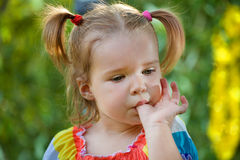 Funny little girl in the park. Sucking her thumb Royalty Free Stock Image