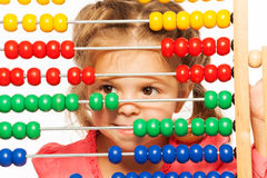 Funny little girl peeping out colorful abacus Royalty Free Stock Photos