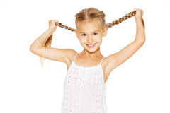 Funny little girl with pigtails. Funny little girl with a charming smile in a white dress holding a pigtails Stock Photo