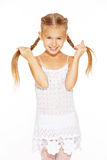 Funny little girl with pigtails. Funny little girl with a charming smile in a white dress holding a pigtails Stock Images