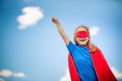 Funny little girl plaing power super hero. Funny little girl plaing power super hero over blue sky background. Superhero concept Royalty Free Stock Photos