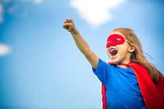 Funny little girl plaing power super hero. Funny little girl plaing power super hero over blue sky background. Superhero concept stock photo