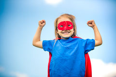 Funny little girl plaing power super hero. Funny little girl plaing power super hero over blue sky background. Superhero concept Royalty Free Stock Images