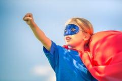 Funny little girl plaing power super hero. Funny little girl plaing power super hero over blue sky background. Superhero concept Royalty Free Stock Photo