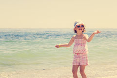 Funny little girl play badminton on the beach. The image is tint Royalty Free Stock Image
