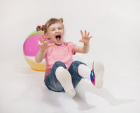 Funny little girl playing with ball. White background Stock Photos