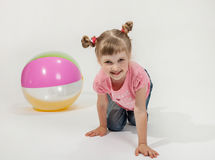 Funny little girl playing with ball. White background Stock Image