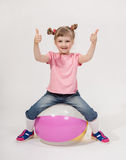 Funny little girl playing with ball. White background Royalty Free Stock Image