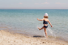 Funny little girl playing on the beach. Selective focus Stock Photo