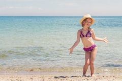 Funny little girl playing on the beach. Royalty Free Stock Images