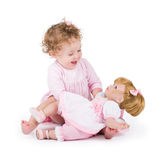 Funny little girl playing with a beautiful doll Royalty Free Stock Image