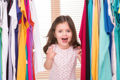 Funny little girl playing with clothes. Royalty Free Stock Photo