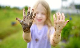 Funny little girl playing in a large wet mud puddle on sunny summer day. Child getting dirty while digging in muddy soil. Messy games outdoors stock photos