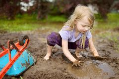 Funny little girl playing in a large wet mud puddle on sunny summer day. Child getting dirty while digging in muddy soil. Messy games outdoors stock photography