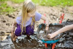 Funny little girl playing in a large wet mud puddle on sunny summer day. Child getting dirty while digging in muddy soil. Royalty Free Stock Photos