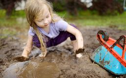 Funny little girl playing in a large wet mud puddle on sunny summer day. Child getting dirty while digging in muddy soil. Messy games outdoors stock image