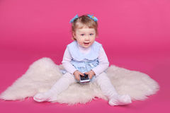 Funny little girl playing with mobile phone over pink background. Studio Stock Photos