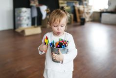 Funny little girl playing with pencils at the kindergarten stock photo