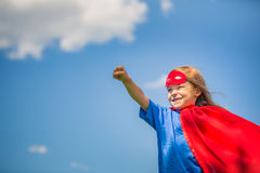 Funny little girl playing power super hero. Stock Photo