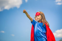 Funny little girl playing power super hero. Stock Image
