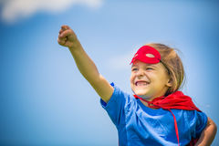 Funny little girl playing power super hero. Stock Images