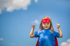 Funny little girl playing power super hero. Royalty Free Stock Photo