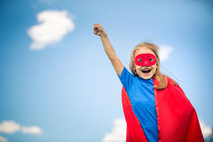Funny little girl playing power super hero. Royalty Free Stock Image