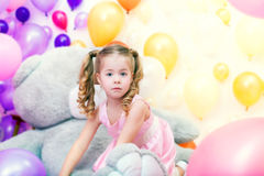 Funny little girl playing in studio with balloons Royalty Free Stock Photo