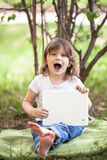 Funny little girl playing with tablet outdoors royalty free stock photography
