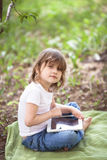 Funny little girl playing with tablet outdoors Stock Photo