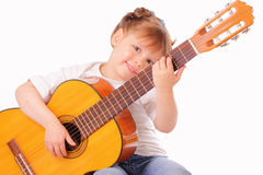 Funny little girl plays guitar Royalty Free Stock Images