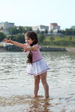 Funny little girl plays with water splashes Royalty Free Stock Photo