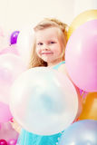 Funny little girl posing with balloons Royalty Free Stock Images