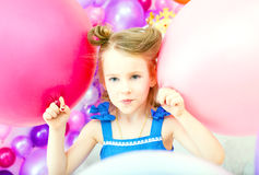 Funny little girl posing with colorful balloons Stock Photos