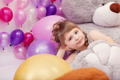 Funny little girl posing lying on big plush bear Royalty Free Stock Photography