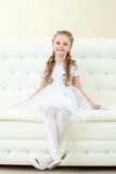 Funny little girl posing sitting on white couch Royalty Free Stock Images