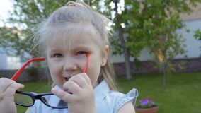 Funny little girl put on her face adult eyeglasses stock video footage