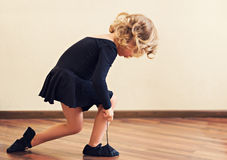 Funny little girl put on shoes for dance. Stock Image