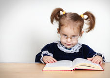 Funny little girl reading book with glasses Stock Photography