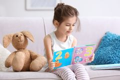 Funny little girl reading book on sofa. At home Royalty Free Stock Image
