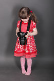 Funny little girl in red dress holds camera stock photography