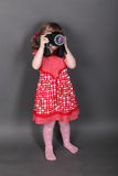 Funny little girl in red dress shoots Royalty Free Stock Photos
