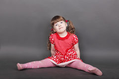 Funny little girl in red dress sits on floor Stock Photos