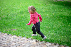 Funny little girl runing on green grass Stock Photos