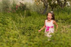 Funny little girl running in the park. Cute little girl running in the park at bright summer day Stock Images