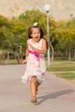 Funny little girl running in the park. Cute little girl running in the park at bright summer day Royalty Free Stock Photos
