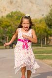 Funny little girl running in the park. Cute little girl running in the park at bright summer day Stock Photography