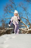Funny little girl running in the snow Royalty Free Stock Photography
